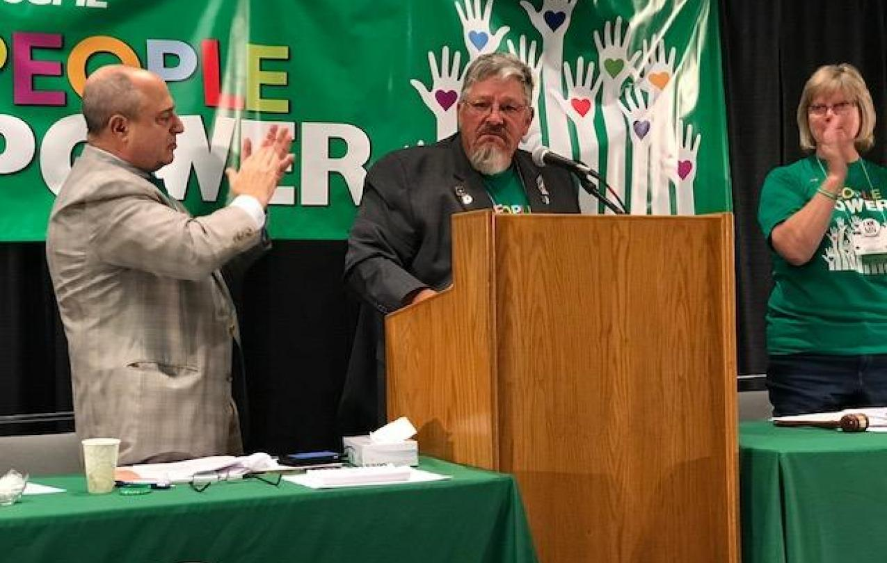 AFSCME Council 5 executive director Eliot Seide and president Judy Wahlberg applaud Council 61 president Danny Homan (center).